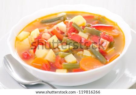 Fresh vegetable soup made of green bean, carrot, potato, red bell pepper, tomato in bowl - stock photo