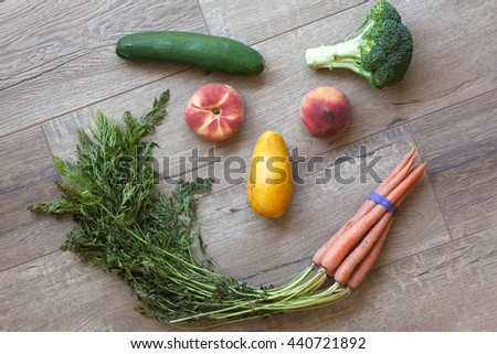 Fresh vegetables and fruits array as a smiley face on wooden table - stock photo