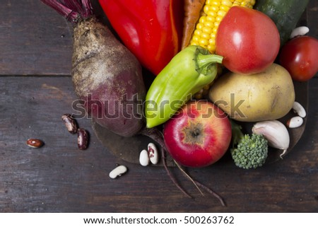 Fresh vegetables and fruits in a basket on a wooden table