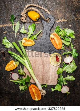 Fresh vegetables and herbs ingredients for tasty cooking around blank cutting board on rustic wooden background, top view - stock photo