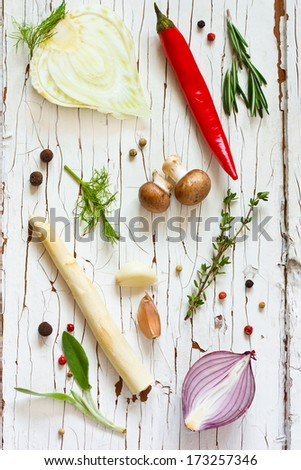 Fresh vegetables and herbs on an old wooden board. - stock photo