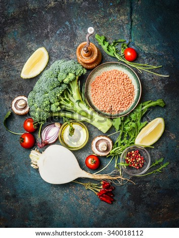 Fresh vegetables and ingredients with red lentil for healthy cooking on rustic background, top view, vertical border. Vegetarian food or diet eating concept. - stock photo