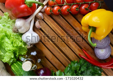 fresh vegetables and olive oil on wooden background