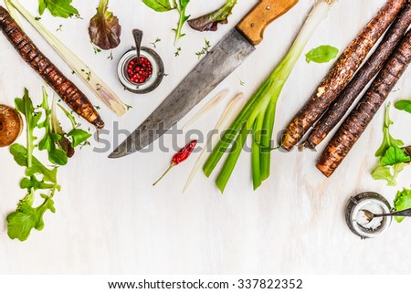 Fresh vegetables and seasoning ingredients for healthy cooking with kitchen knife on white wooden background, top view, border  - stock photo