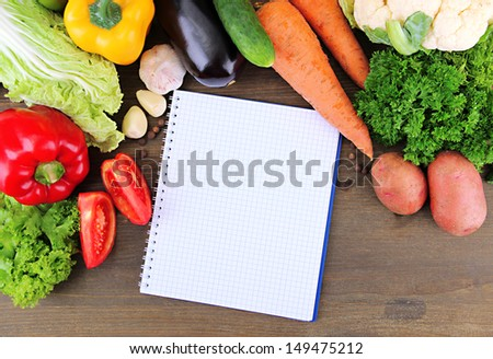 Fresh vegetables and spices and paper for notes, on wooden background
