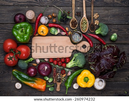 Fresh vegetables and spices: tomatoes, peppers, mushrooms, herbs, nuts on wooden background