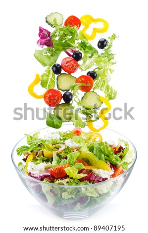 fresh vegetables, as salad ingredients, falling into bowl on white background - stock photo