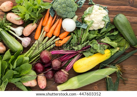 fresh vegetables: beet, carrot, zucchini, broccoli and others on wooden background, top view