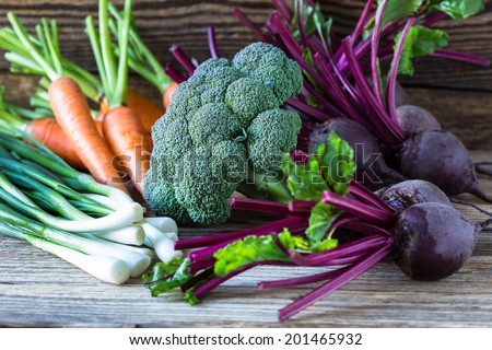 Fresh vegetables carrots, beetroots, broccoli, green onion on  wooden background. Harvest still life - stock photo