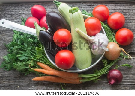 fresh vegetables from the garden - eggplant, zucchini, onions, carrots, parsley and tomatoes - stock photo