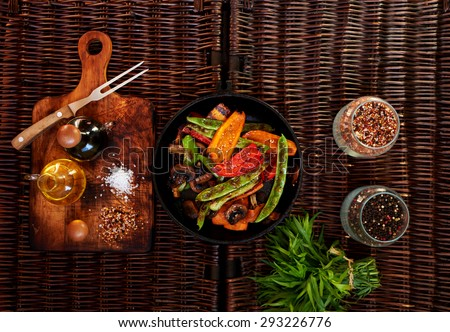 Fresh vegetables grilled, housewife put them in a deep cast-iron cookware, near a fresh bunch of rosemary, it will add it to the very end when refuel vegetable sauce of garlic and olive oil - stock photo