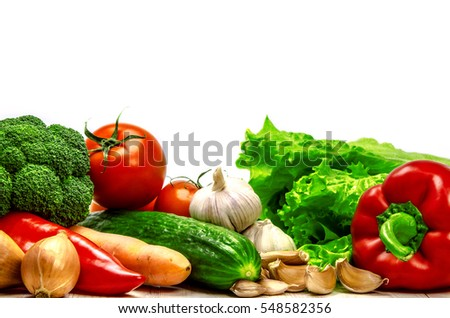 Fresh vegetables, herbs, onions and garlic on a wooden surface.