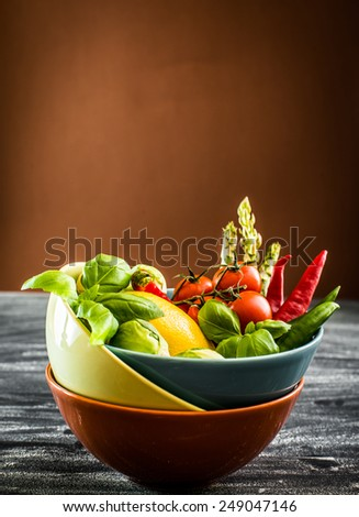 Fresh vegetables in a bowl on the table with brown background - stock photo