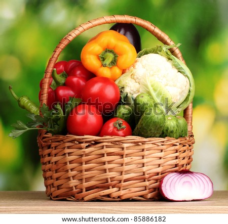 Fresh vegetables in basket on  wooden table on green background - stock photo