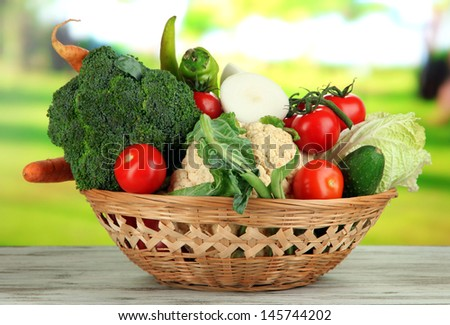 Fresh vegetables in basket on wooden table on natural background