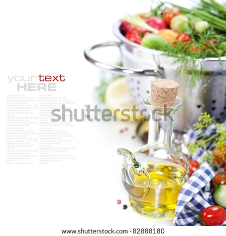 Fresh vegetables in metal colander and olive oil over white (with sample text)
