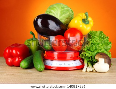 Fresh vegetables in scales on table on orange background - stock photo