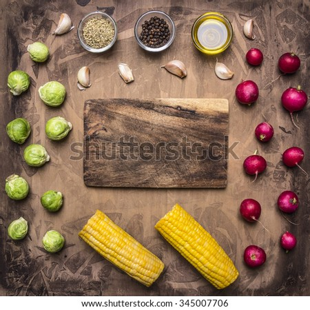 Fresh vegetables ingredients radishes, brussels sprouts, corn, seasoning lined around the cutting board on wooden rustic background top view place for text - stock photo
