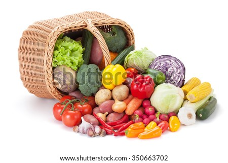 Fresh vegetables next to the overturned basket, isolated on the white background. - stock photo