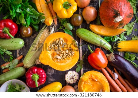 Fresh vegetables on a dark table. Autumn background. Healthy eating. Sliced pumpkin, zucchini, squash, bell peppers, carrots, onions, garlic, tomatoes, eggplant, corn cob, rucola and basil. Top view - stock photo