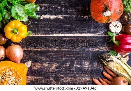 Fresh vegetables on a rustic dark textured table. Autumn background. Healthy eating frame. Sliced pumpkin, zucchini, squash, bell peppers, carrots, onions, garlic, tomatoes. Top view. Space for text - stock photo