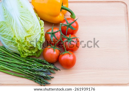 Fresh vegetables on wooden cutting board, healthy food. - stock photo