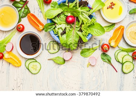 Fresh vegetables salad with various dressing on light rustic background, top view, border. Healthy lifestyle and vegetarian or diet  food concept - stock photo