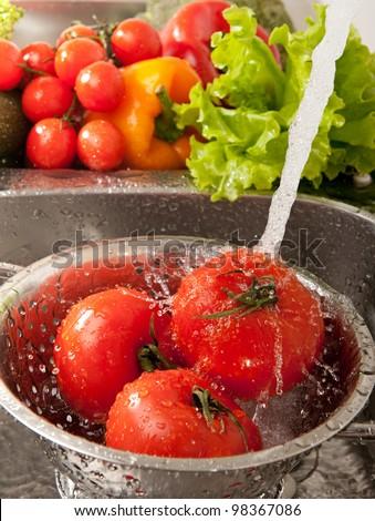 Fresh vegetables splashing in water before cooking - stock photo