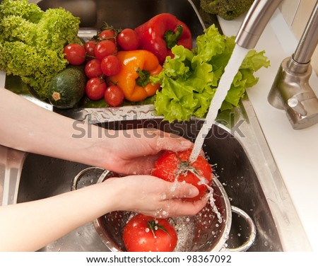 Fresh vegetables splashing in water before cooking - stock photo