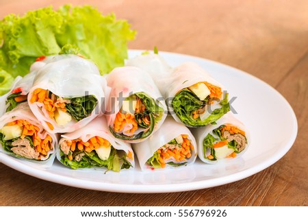 fresh vegetables spring rolls on white plate, wood table background.
