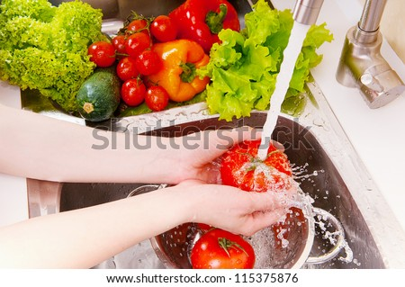 Fresh vegetables under water stream in colander - stock photo