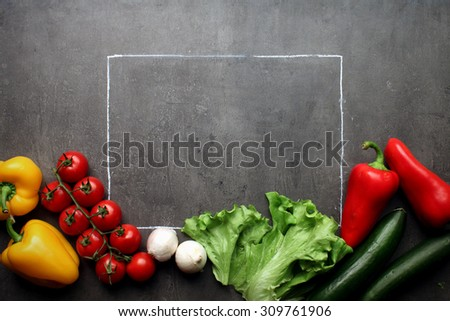Fresh vegetables with chalk frame on grey kitchen table - stock photo