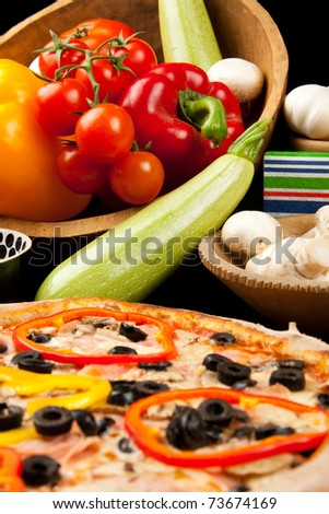 Fresh vegetables with tasty pizza in foreground - stock photo