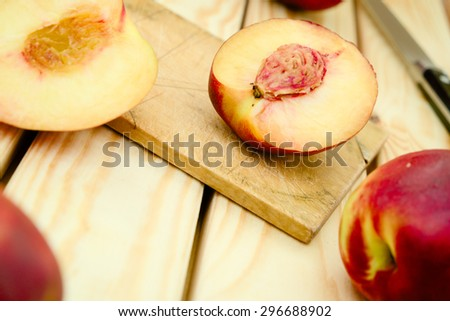 Fresh, vegetarian, juicy red and yellow sliced and whole nectarines on a cutting board with the knife in the background - stock photo