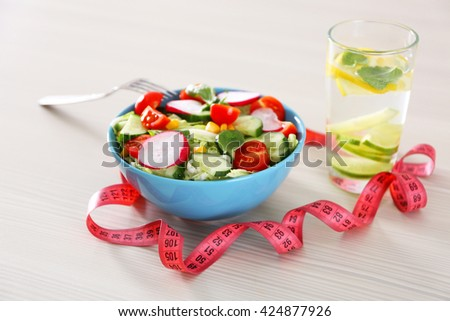 Fresh vegetarian salad and glass of lemonade on wooden table closeup - stock photo