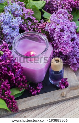 fresh violet lilac flowers with candle and aromaric oil - stock photo