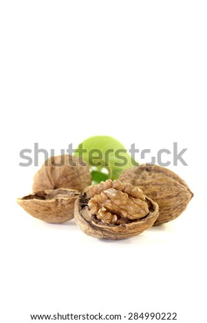 fresh walnuts with walnut leaves on a bright background - stock photo