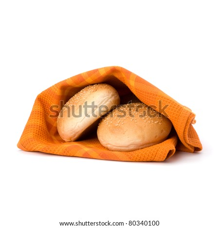 Fresh warm bread over kitchen towel isolated on white background