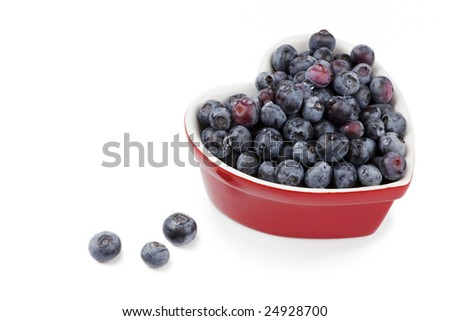 Fresh washed blueberries in a a red heart shaped bowl, isolated on white