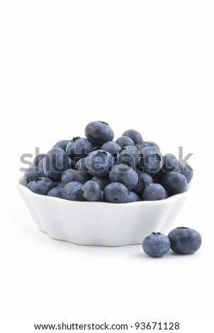 Fresh washed blueberries in small white dish, vertical format