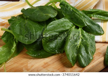 Fresh washed organic spinach on a cutting board - stock photo
