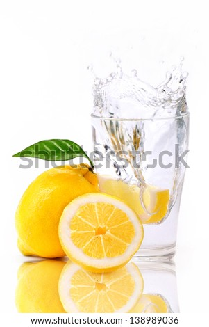 fresh water in glass with splashed lemon - stock photo