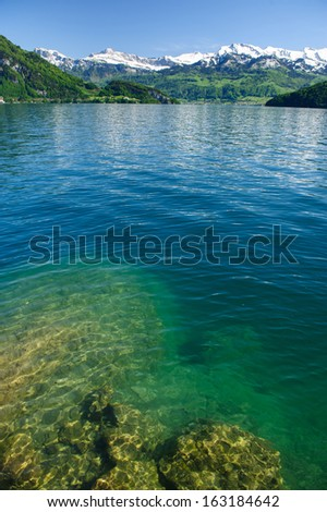 fresh-water lake surrounded with mountains in a sunny day, Switzerland