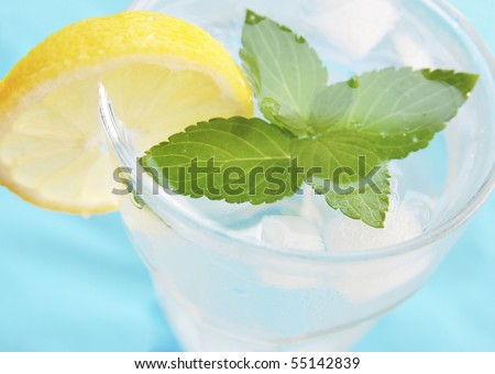 Fresh water with ice cubes, mint and lemon slice - stock photo