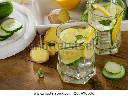 Fresh water with lemon, mint  and cucumber  on a wooden background. Selective focus - stock photo