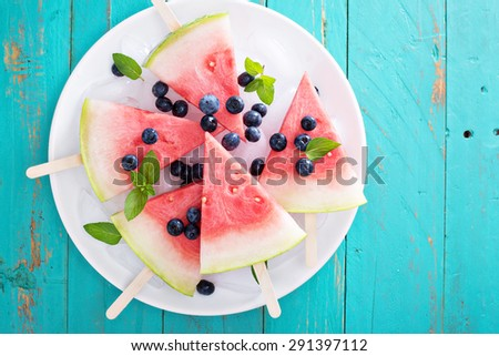 Fresh watermelon popsicles with blueberries cut on ice top view - stock photo