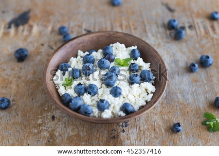 Fresh white cottage cheese with Juicy blueberries on wooden background in bowl. Healthy eating and nutrition. Dietary breakfast for summer time selective focus - stock photo
