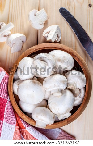 Fresh white mushrooms in a wooden bowl ready to be cleaned. - stock photo