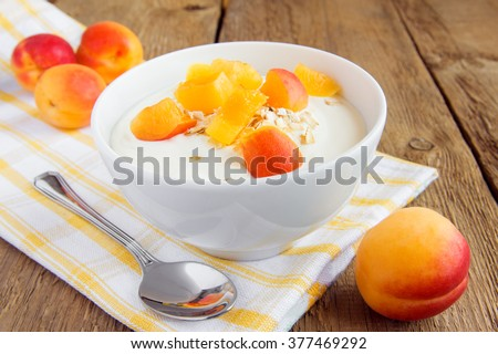 Fresh white yogurt in bowl with apricots and oat flakes (granola) over rustic wooden background. Healthy breakfast, copy space. - stock photo