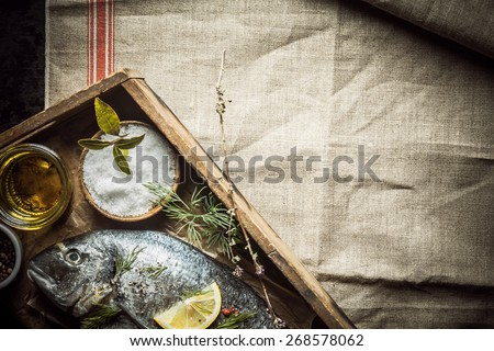 Fresh whole fish and rubbing spice and assorted fresh herbs lying on an old wooden tray ready to be marinated before cooking for dinner, overhead view on a creased cloth with copyspace - stock photo